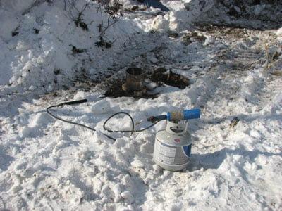Фото: Использование паяльной лампы для разморозки труб